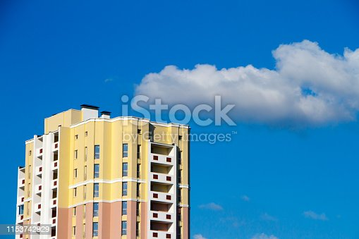 New block of modern apartments with balconies and blue sky in the background, free space for text