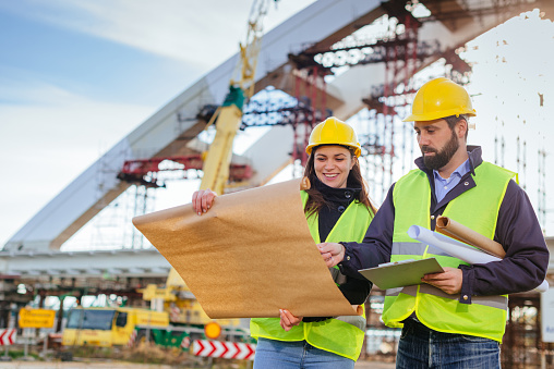 Two engineers, male and female, in protective helmets and reflective clothing, standing on construction site where large arch bridge is being built. Engineers looking at blueprints, planning and discussing project development.