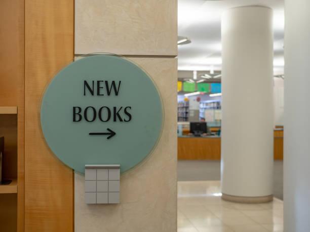 neue bücher-wegweiser nach rechts mit bibliothek im hintergrund - bibliothekschilder stock-fotos und bilder