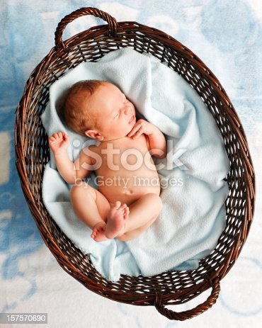 Lying in a woven basket is a sleeping infant baby boy. He is lying on a soft blue blanket which is in the basket and the basket is on a blue blanket as well.