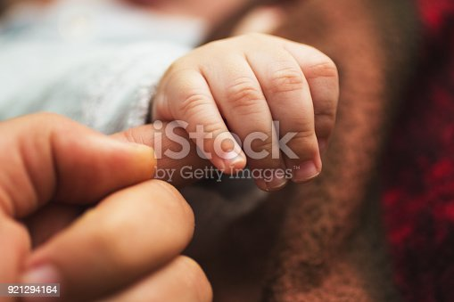 istock New born baby holding his father finger 921294164