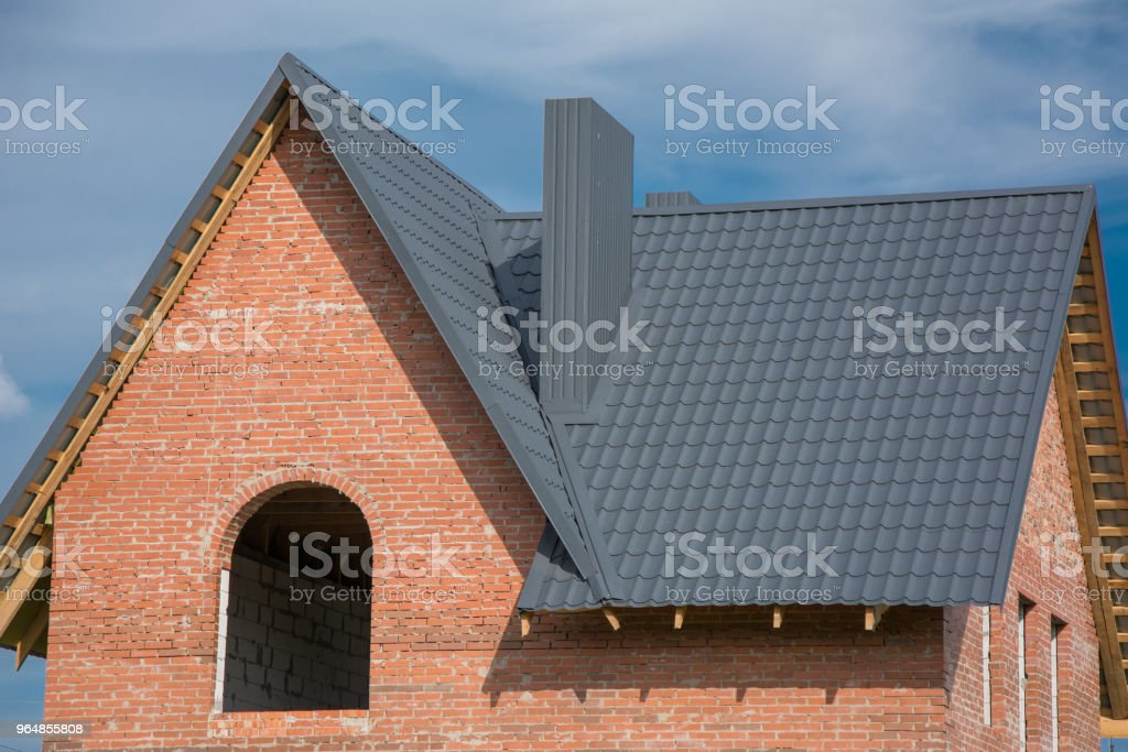 new brick home under construction over blue sky royalty-free stock photo