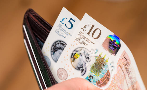 New British ten pound and five pound polymer notes in a wallet Edinburgh, UK - Closeup of a person opening a leather wallet to pay with newly issued British polymer banknotes, featuring holographic security features, and a watermark of Queen Elizabeth II's image. ten pound note stock pictures, royalty-free photos & images