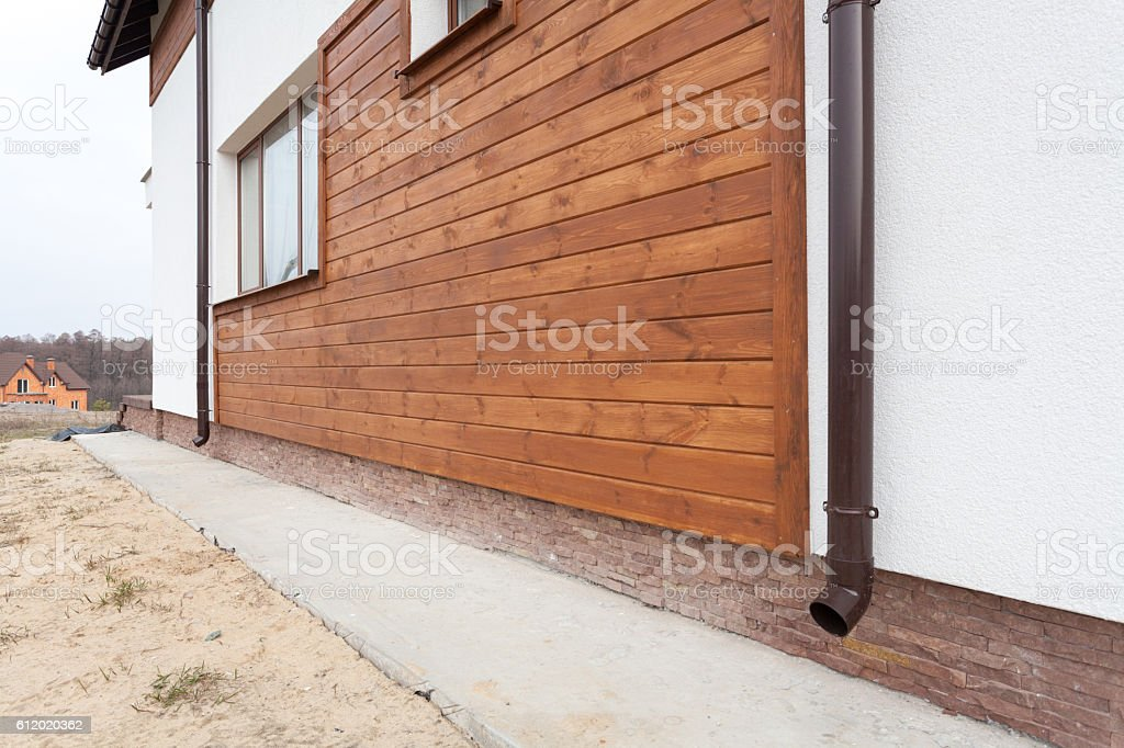 New brown copper gutter in house with wooden planks stock photo