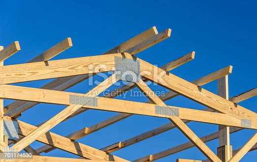Roof with a wooden truss framework with a blue sky background.