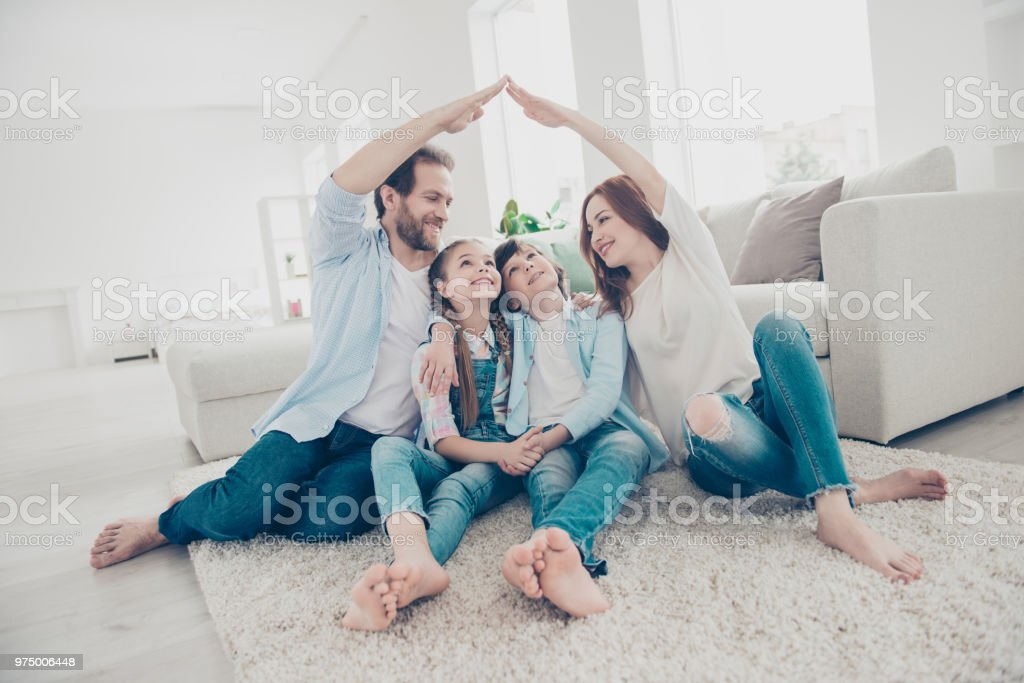 New building residential house purchase apartment concept. Stylish full family with two kids sitting on carpet, mom and dad making roof figure with hands arms over heads стоковое фото