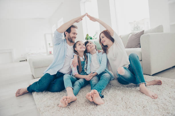 New building residential house purchase apartment concept. Stylish full family with two kids sitting on carpet, mom and dad making roof figure with hands arms over heads stock photo