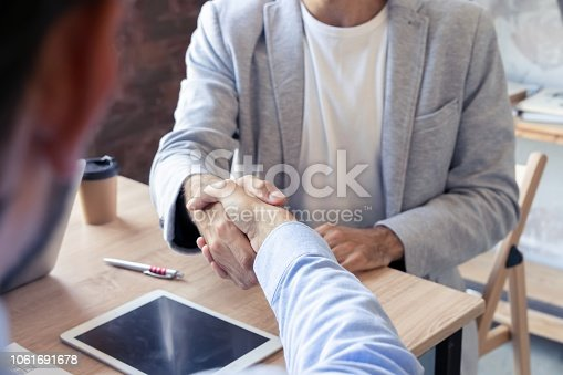 istock New business partners. Young modern colleagues in smart casual wear shaking hands and smiling while sitting in the creative office. 1061691678