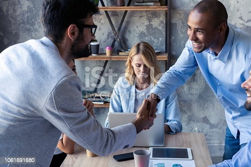 istock New business partners. Young modern colleagues in smart casual wear shaking hands and smiling while sitting in the creative office. 1061691680
