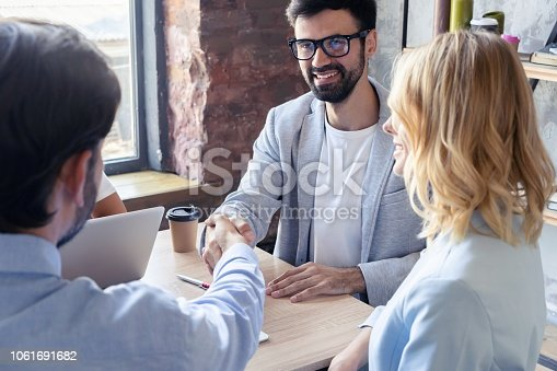 istock New business partners. Young modern colleagues in smart casual wear shaking hands and smiling while sitting in the creative office. 1061691682
