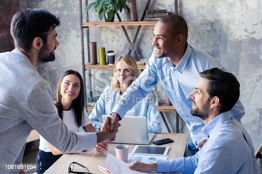istock New business partners. Young modern colleagues in smart casual wear shaking hands and smiling while sitting in the creative office. 1061691694
