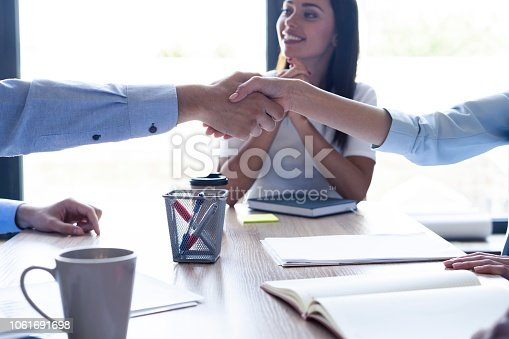 istock New business partners. Young modern colleagues in smart casual wear shaking hands and smiling while sitting in the creative office. 1061691698