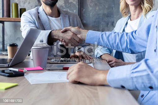 istock New business partners. Young modern colleagues in smart casual wear shaking hands and smiling while sitting in the creative office. 1061691700