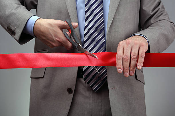 New business venture cutting a red ribbon Cutting a red ribbon with scissors concept for new business venture or opening ceremony bureaucracy stock pictures, royalty-free photos & images