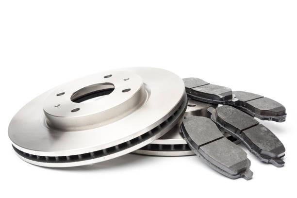 nouveau disque de frein de voiture et plaquettes de freins isolé sur blanc - disque de frein photos et images de collection
