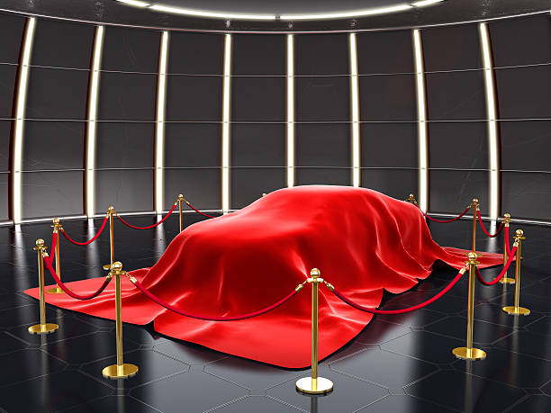 New car model exhibition New model covered with red velvet with stanchion ropes and pole barriers.Similar: car show stock pictures, royalty-free photos & images