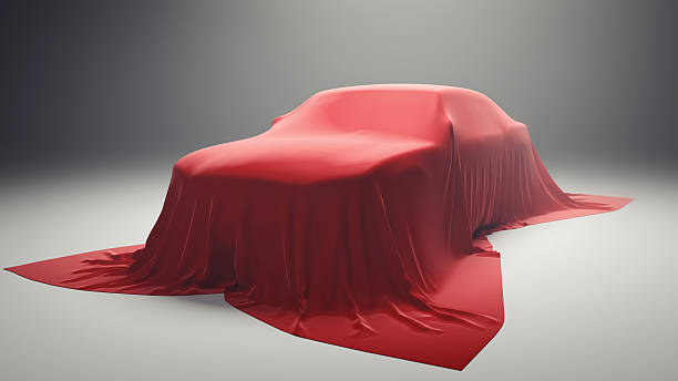 New Car Model Presentation A sedan car covered with red velvet cloth. Conceptual image for new car model presentation or car as a gift. covering stock pictures, royalty-free photos & images