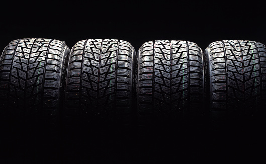 close up on a pile of four new car tires on black background