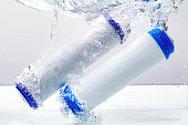 New carbon filter cartridge for house water filtration system isolated on white background. Splash. Concept.