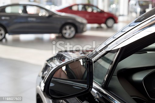New cars at dealer showroom. Themed blur background with bokeh effect. Car auto dealership. Prestigious vehicles.