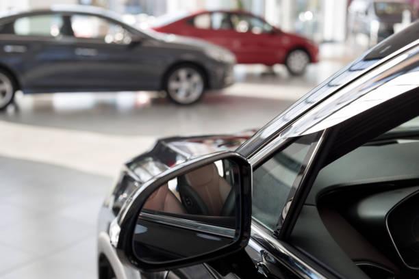 nuove auto presso lo showroom del concessionario. sfondo sfocato a lisce con effetto bokeh. concessionaria auto. - auto foto e immagini stock