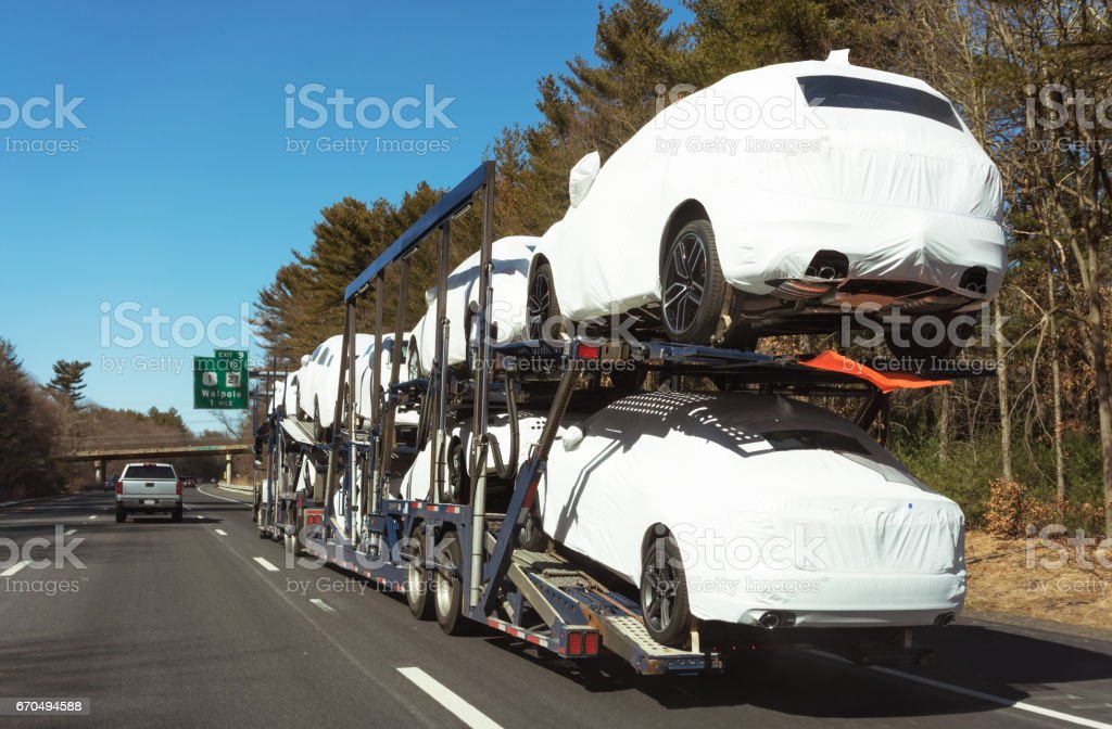 New cars being delivered by a car transporter truck on the freeway stock photo