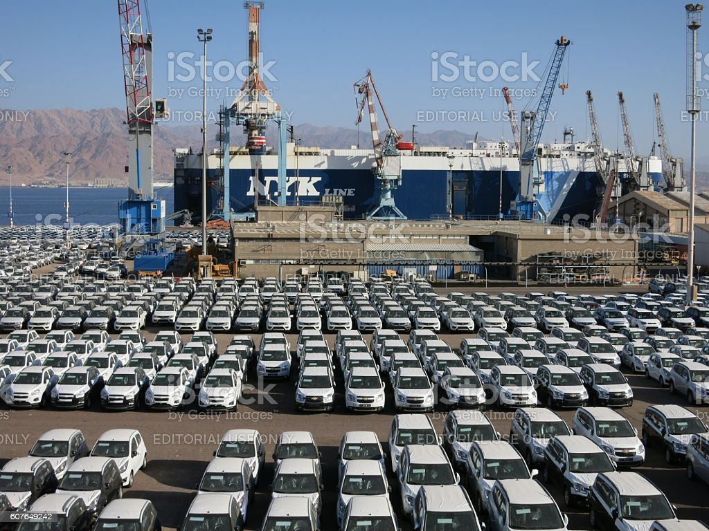Rows of new cars covered in protective white sheet parked in cargo...