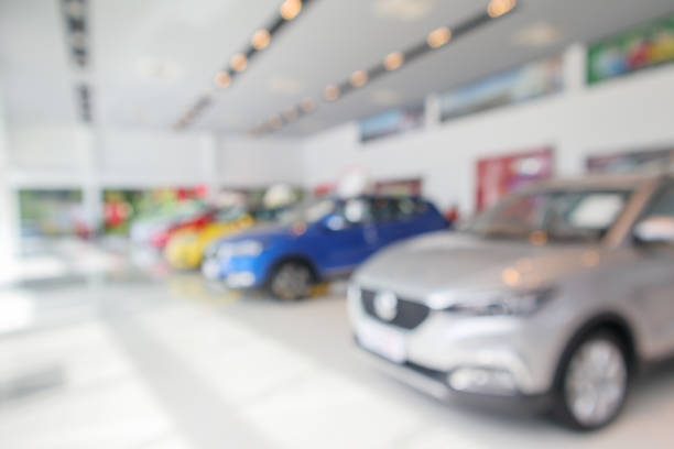 new cars in showroom blurred defocused background new cars in showroom blurred defocused background car salesperson stock pictures, royalty-free photos & images