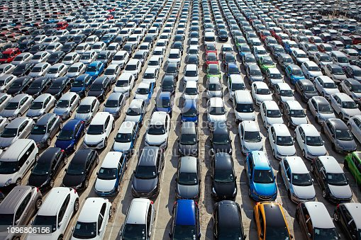Barcelona, Spain - April 10, 2018:  Aerial view of new modern passenger cars stored on large parking lot in the Port de Barcelona waiting for their next distribution.
