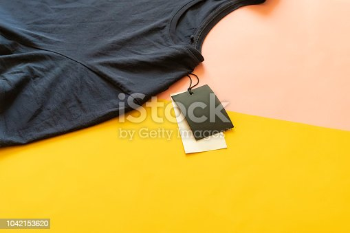 istock new casual t-shirt with sale price tag with copy space isolated on pink and yellow background f 1042153620