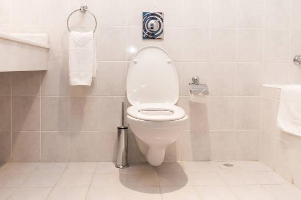 New ceramic toilet bowl near light wall stock photo