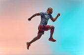 istock New champion. Full length of young african man in sports clothing jumping against colorful background 1176741202