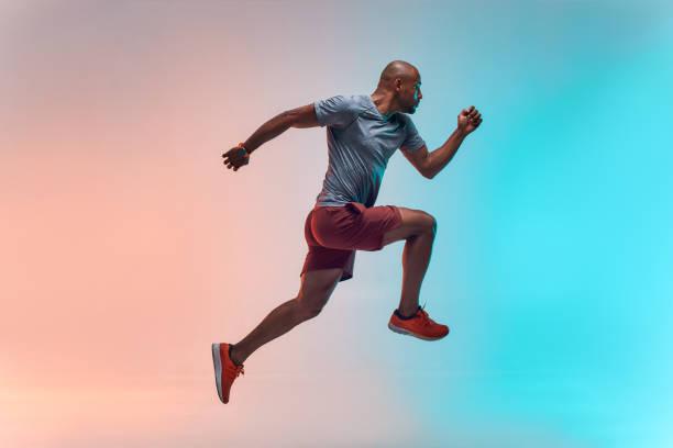 nieuwe kampioen. volledige lengte van de jonge afrikaanse man in sportkleding springen tegen kleurrijke achtergrond - atleet stockfoto's en -beelden
