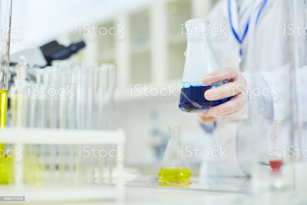 Close-up of unrecognizable chemist in protective glove holding flask...
