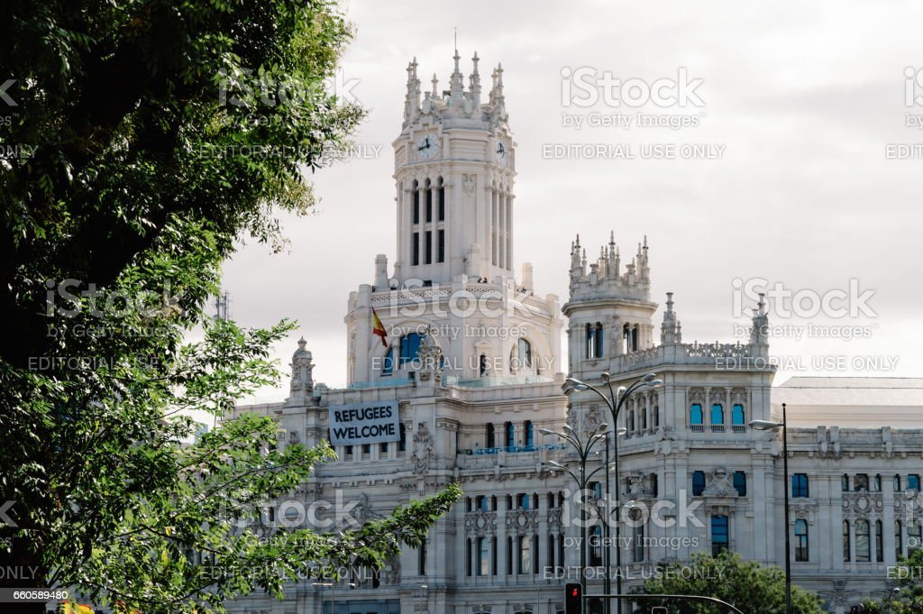 New City Hall of Madrid with a banner with the words Refugees Welcome stock photo