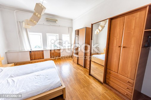 New clean white bed simple plain minimalist with light wood wooden wardrobe cabinet closet or armoire, in bedroom in staging model home, house or apartment, windows bright