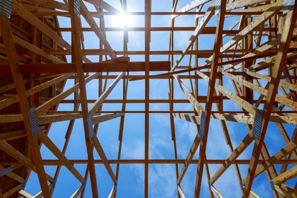 New construction home framing against blue sky, closeup of ceiling frame. stock photo