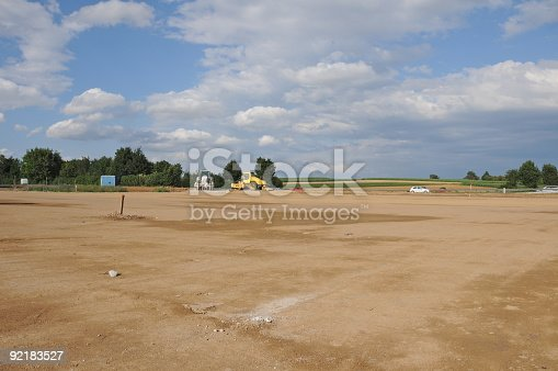 The site is cleared, flattened by bulldozers and ready for development. Building area in the country. Farmland had to yield, the soil will be sealed. The ground has been levelled and prepared for rising a factory or new homes. Wide, empty space. Blue cloudy sky. Trees, bushes, highway and construction machinery in the distance. Horizontal orientation.