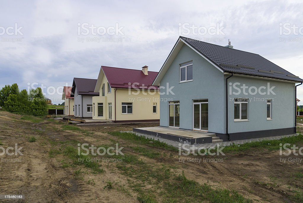 New cottages with green grass near the road stock photo