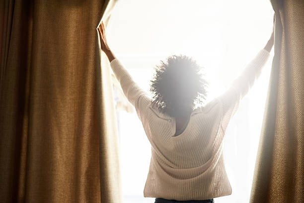 New day, new possibilities Rearview shot of a woman opening the curtains on a bright sunny day routine stock pictures, royalty-free photos & images
