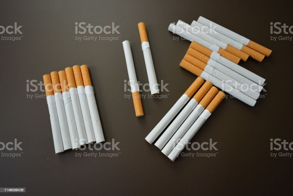 New decomposed many cigarettes on a brown matte background. stock photo
