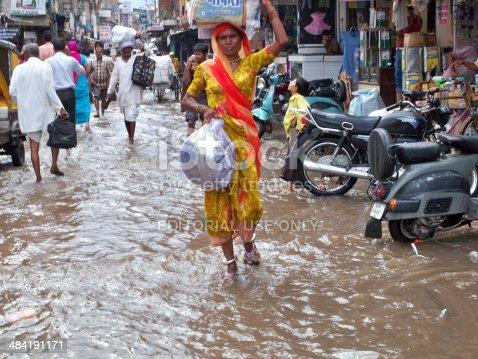 New Delhi, India - January 6, 2008: Women and men walking in flooded New Delhi street during monsoon season.