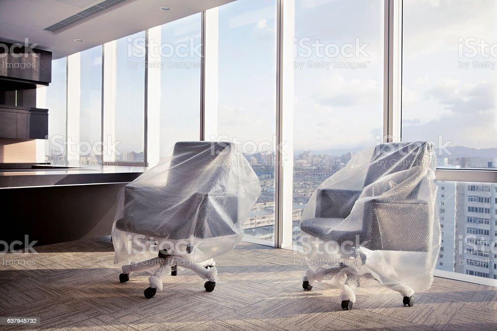 New desk chairs wrapped with bubble wrap in executive office stock photo
