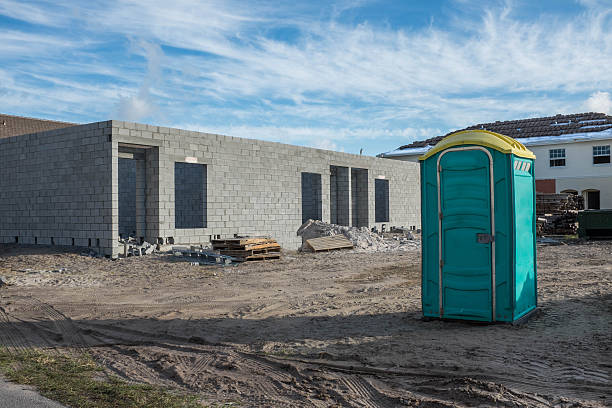New Development Construction Zone with Outhouse Green outhouse for workers is seen on the unpaved dirt section of a construction zone with duplexes being built. portable toilet stock pictures, royalty-free photos & images