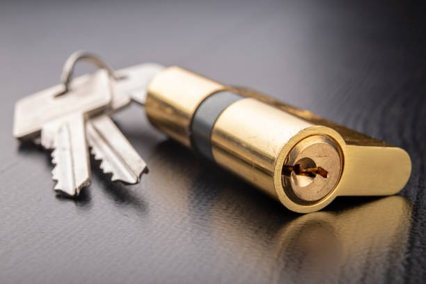 A new door lock on a dark background. A patent and keys to secure the front door. A black background. A new door lock on a dark background. A patent and keys to secure the front door. A black background. locksmith stock pictures, royalty-free photos & images