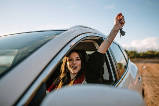 New driver A young woman showing the car keys through the car window car stock pictures, royalty-free photos & images