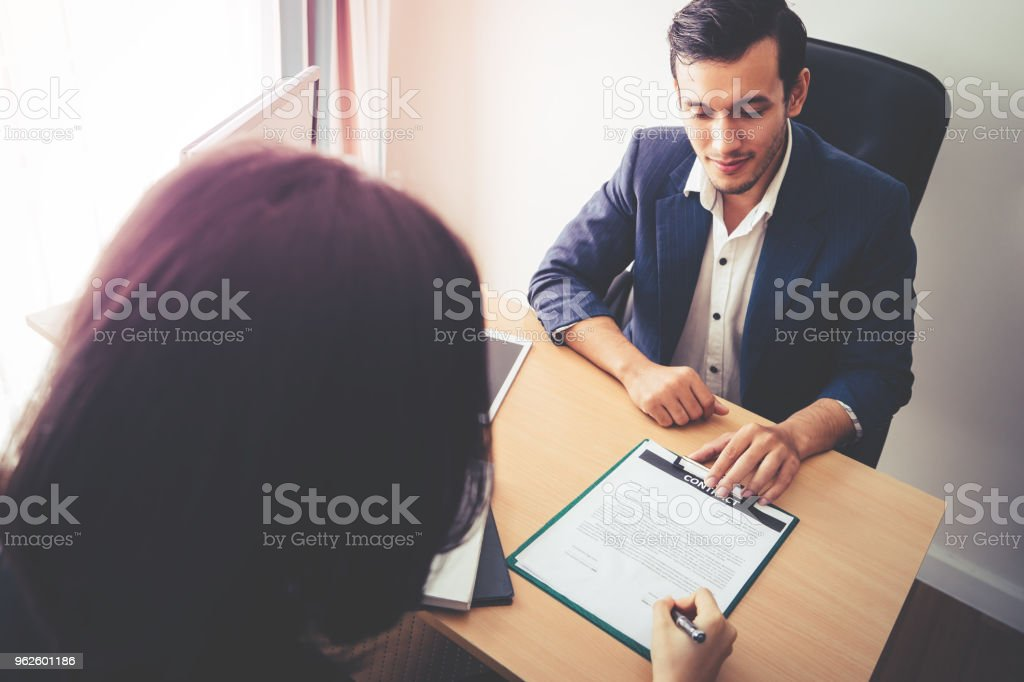 New Employer have been invited to sign work contract after successful job interview stock photo