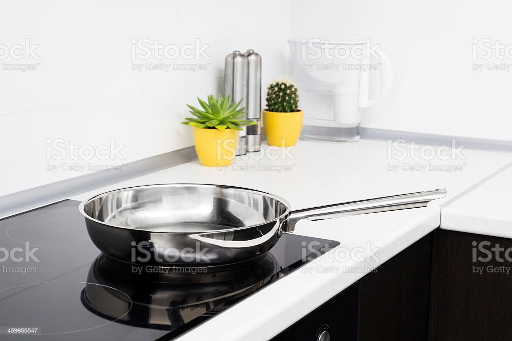 New empty frying pan in modern kitchen with induction stove stock photo