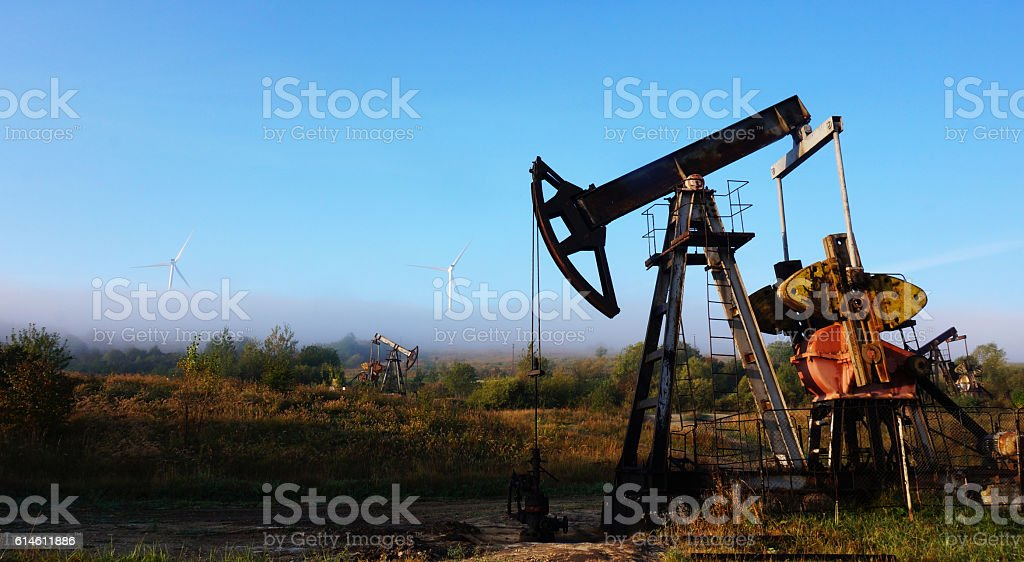 New energy era is coming. An old oil pump jack in front of modern wind turbines and low fog Blade Stock Photo