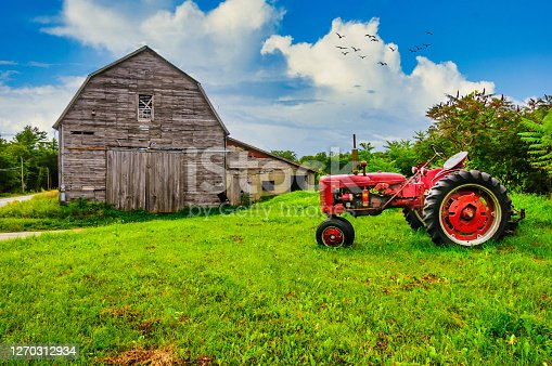 A red tractor is parked in the grass outside an old abandoned wooden barn in Northern New England.